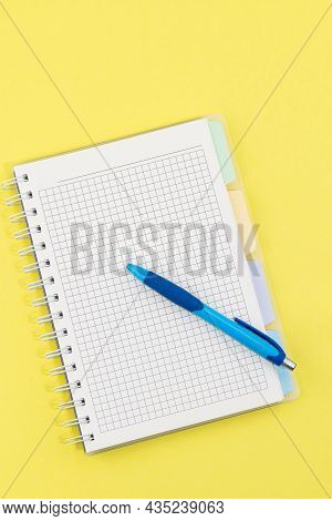 Blank Notebook And Pen On Yellow Background.