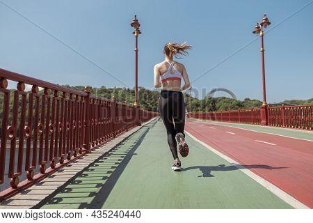 Slim Sportswoman Runs Along Footbridge Training On Sunny Summer Day