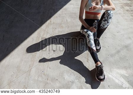 Sportswoman With Bottle Of Water Checks Time On Smartwatch Sitting On Concrete Ground Closeup