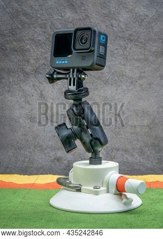 Fort Collins, CO, USA - October 3, 2021: GoPro Hero 10 black, waterproof action camera on a popular articulated RAM mount and suction cup by SeaSucker against abstract paper landscape.