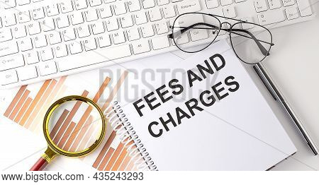 Fees And Charges Text Written On Notebook With Keyboard, Chart,and Glasses
