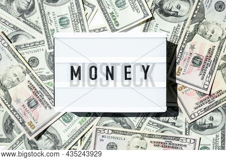 Lightbox Board With The Word Money In Black Letters Around Us Dollars Banknotes. Finance Background.