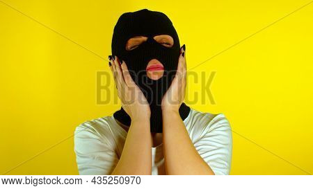 Close Up Of Unrecognizable Woman In Black Balaclava Stroking Her Head And Face On Yellow Background.