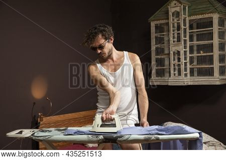 Young man alone in his home ironing a shirt in a white tank top and in his underwear.