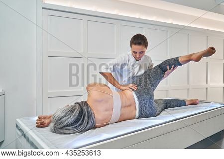 Concentrated Brunette Osteopath Doing Muscle Treating Exercises