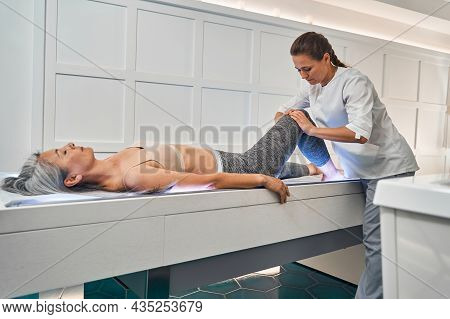 Female Doctor Hands Giving Physiotherapy To Patient Knee