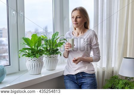 Middle-aged Woman With A Glass Of Milk, At Home Near The Window