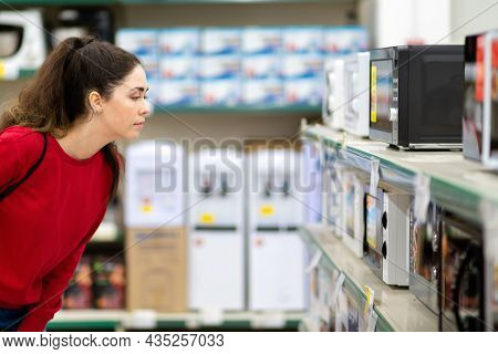 Portrait Of A Young Beautiful Woman Chooses A Microwave Oven In A Home Appliance Store. Side View. T
