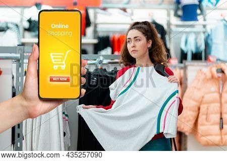 Portrait Of A Young Thoughtful Caucasian Woman Choosing Clothes In A Store. On The Left Side Is A Ha