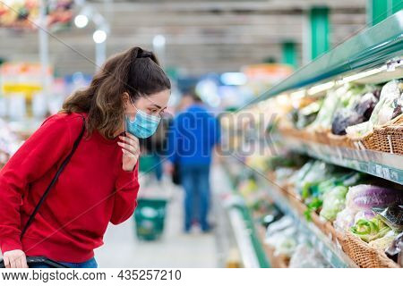 Shopping During The Coronavirus Pandemic. A Young Woman In A Medical Mask On Her Face Looks At Veget