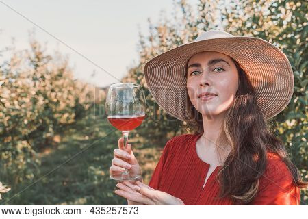 Wine Tasting And Relaxing In The Garden. Young Beautiful Brunette Full Face In A Red Dress And Hat W