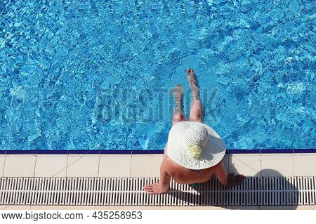 Woman In Sun Hat And Bikini Sitting On The Edge Of Swimming Pool And Dangling Her Legs In Water, Top