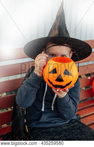 Halloween Kids. Cute Little Boy, Child Wearing A Witch Hat With Orange Bucket Of Jack O Lantern Swee
