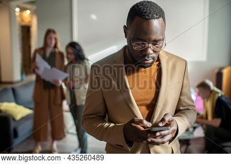 Serious African businessman scrolling in smartphone against group of Caucasian co-workers