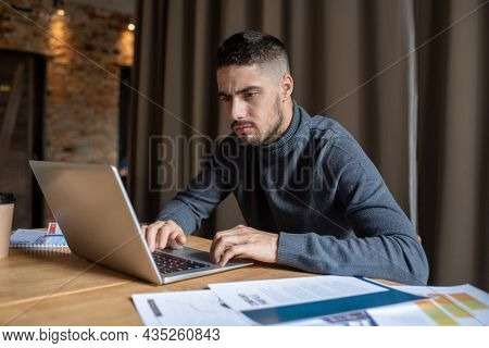 Serious male freelancer concentrating on remote work while sitting in front of laptop