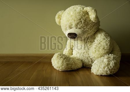 Sad Teddy Bear Sitting Alone On The Floor Loneliness And Child Abuse Concept.