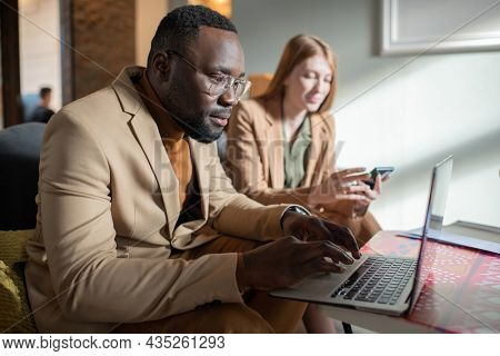 Young serious African man in eyeglasses and formalwear looking at laptop screen against female co-worker