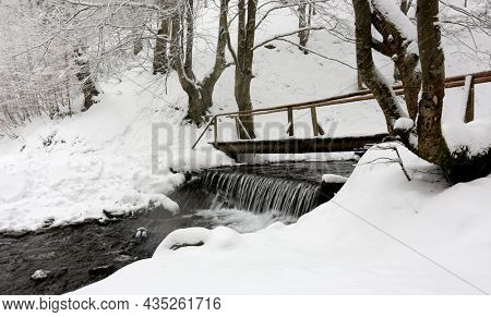 wooden bridge over stream in winter forest during snowfall. Carpathians, Ukraine