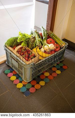 Fruit and Vegetable delivery box on a doormat in front of a door to the house