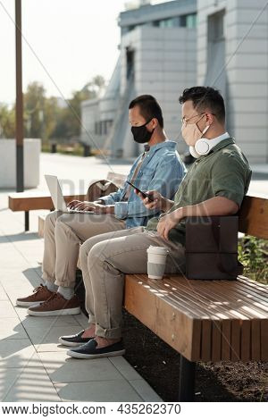 Two young Asian co-workers with mobile gadgets sitting on bench in urban environment