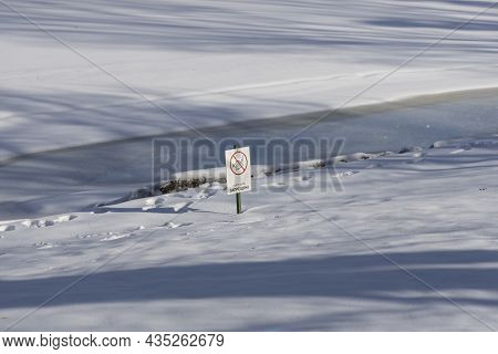 Winter River Covered With Snow And Ice And A Warning Sign