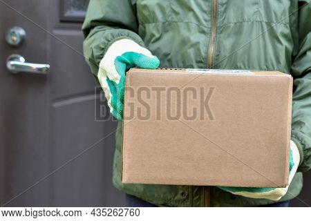 Parcel Cardboard Box In The Hands Of The Postman On The Background Of The Door Of The House. Deliver