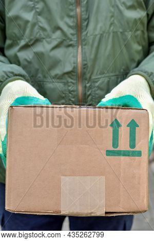Courier Is Holding A Parcel With A Fragile Symbol On A Cardboard Box. Delivery Of The Parcel Courier