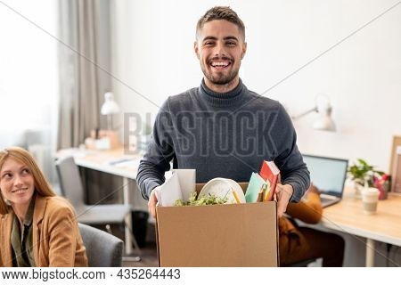 Young cheerful employee with box containing office supplies standing against co-workers