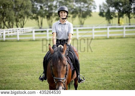 Female Horseman Riding Brown Thoroughbred Horse On Green Meadow In Countryside. Concept Of Rural Res