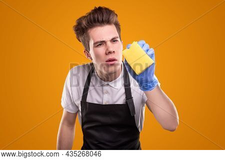 Funny Young Man In Black Apron And Gloves Wiping Invisible Object With Sponge While Cleaning House D