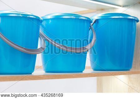 Three New Plastic Blue Utility Buckets With Lid On The Shelf. Industrial Background With Household G