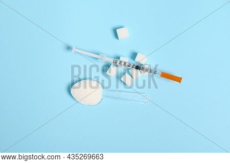 Top View Of Scattered White Sugar On Transparent Measuring Spoon And Insulin Syringe On White Pure R