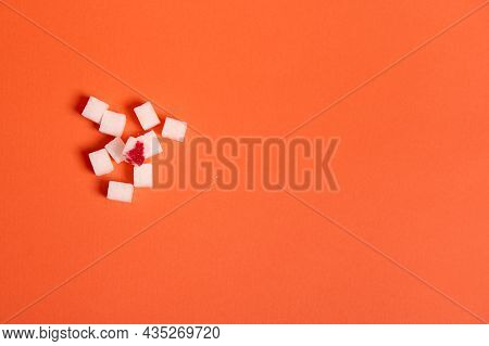 Flat Lay Studio Shot Of Refined White Sugar Cubes With Blood Drop Isolated Over Colored Orange Backg