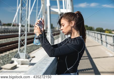Young Happy Self Loved Sporty Fitness Runner Woman Standing And Taking A Break With Bottle Of Water