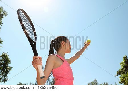 Woman Playing Tennis Outdoors, Low Angle View