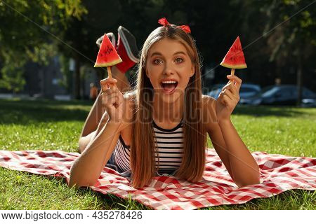 Beautiful Girl With Pieces Of Watermelon On Picnic Blanket In Park