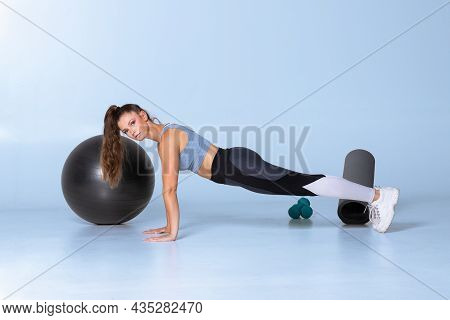 Female Fitness Trainer Standing In Plank With Strong Back On Blue Background Showing Exercise Lookin