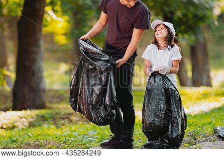 Smiling Beautiful Girl And Adult Man Volunteer Gathering Rubbish Together Outdoors In Gloves Using G