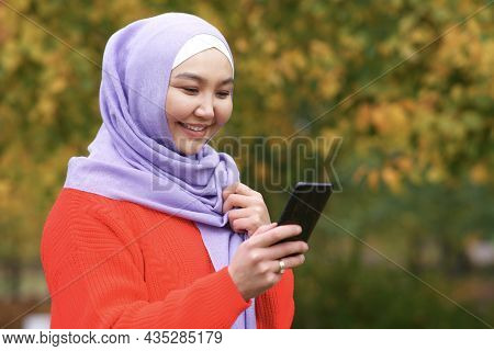 Portrait Of Happy Beautiful Asian Muslim Young Woman Islamic Girl Is Wearing Hijab Scarf Holding Cel