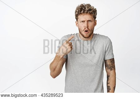 Shocked Blond Guy Gasps Offended, Pointing Finger At Himself And Staring Insulted At Camera, Standin