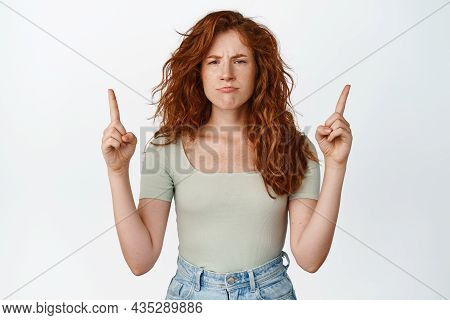 Portrait Of Moody Redhead Girl Sulking, Pointing Fingers Up At Smth Unfair, Being Disappointed, Stan