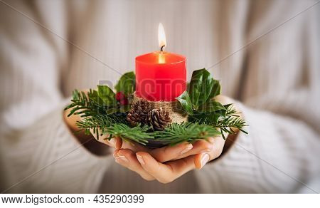 Close up of young woman hands holding red christmas candle with festive decor. Girl hands holding burning candle with holly and branches of fir. Hands of young woman holding burning advent light.