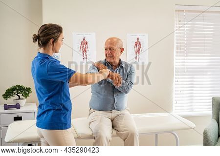Physiotherapist helping senior man with elbow exercise in clinic. Chiropractic checking elbow and shoulder joint pain of old patient. Elderly man undergoing physiotherapy treatment for shoulder injury