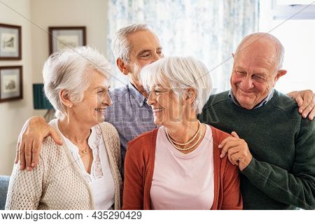 Happy senior couple with friends embracing and smiling at home. Cheerful senior men and beautiful women enjoying being together in eldercare facility centre: serene retirement and carefree concept.
