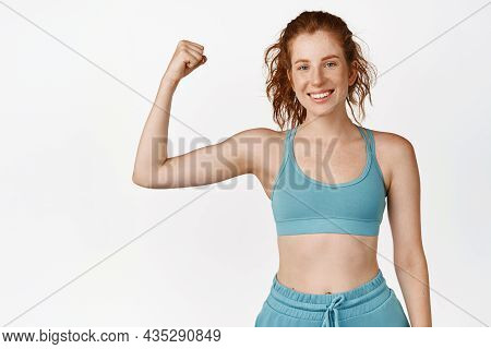 Active And Healthy Redhead Sportswoman Flexing Biceps And Smiling. Fitness Girl Workout, Showing Mus