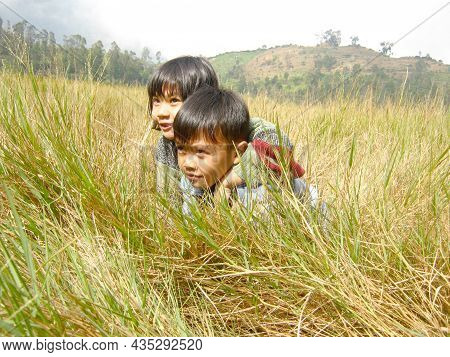 Dieng, Central Java, Indonesia. August 17th 2011. Brother And Sister Playing In A Savanna In Dieng P