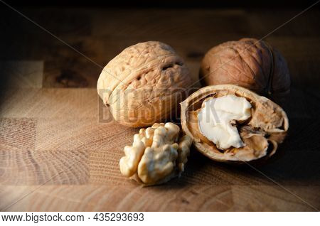 Kernel Of Young Walnut Lies Next To Nuts In Shell On Brown Wooden Background With Copy Space. Harves