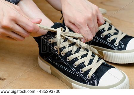 Female Hands Tying Shoelaces On Sneakers, Close-up
