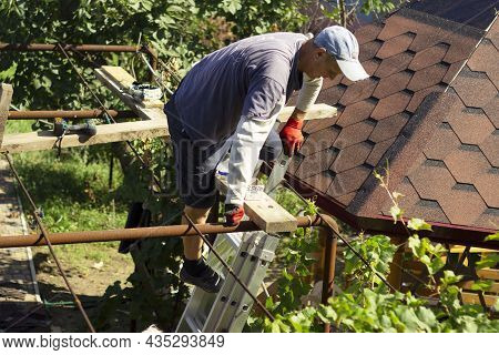 The Roofer Climbs The Stairs To The Roof Of The Gazebo To Continue Roofing Work