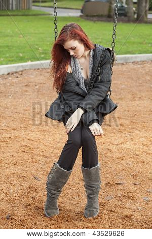 Very Unhappy Young Woman With Beautiful Auburn Hair On A Swing